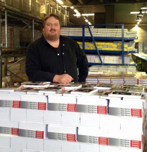 """Julian Reischl mit der Erstauflage seines ersten Buches """"Kindle Fire"""" im Lager des Pearson-Verlages, München."""